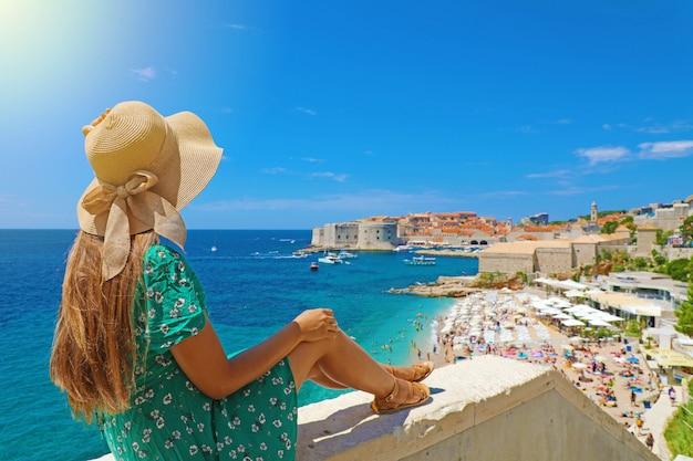 Красивая молодая женщина в шляпе сидит на стене, глядя на потрясающую панорамную деревню дубровник в хорватии, европе