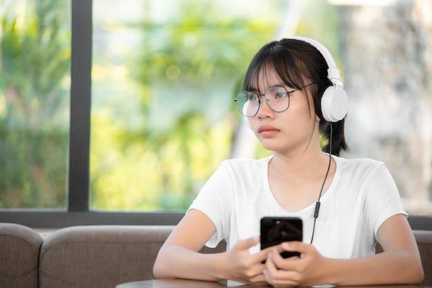 Красивая молодая женщина с наушниками, расслабляющимися в комнате, она слушает музыку с помощью смартфона, расслабления и концепции досуга