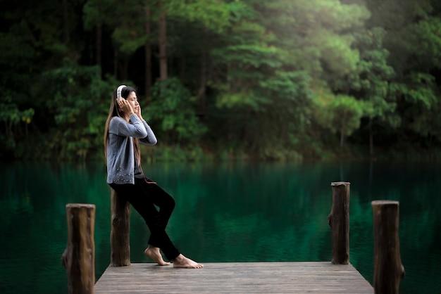 독에서 편안한 헤드폰으로 아름 다운 젊은 여자, 그녀는 음악을 듣고있다