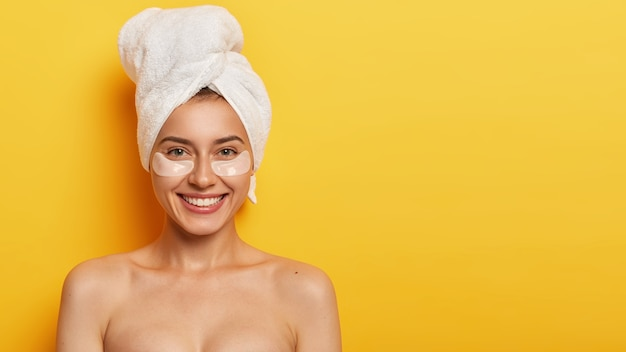 Beautiful young woman with healthy delicate fresh skin under eyes, wears towel on head, applies patches for reducing fine lines, stands naked against yellow wall. spa treatment