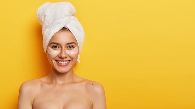 目の下の健康で繊細な新鮮な肌を持つ美しい若い女性は、頭にタオルを着用し、細い線を減らすためのパッチを適用し、黄色の壁に裸で立っています。スパトリートメント