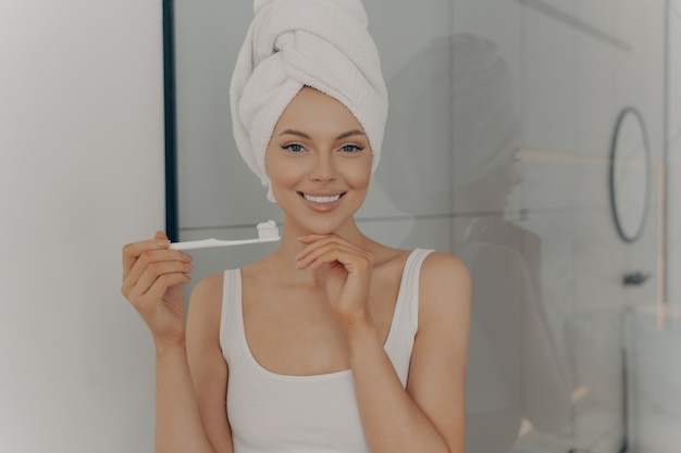 健康的な完璧な笑顔で歯を磨き、カメラでポーズをとる美しい若い女性、自宅のバスルームに立っている頭に白いバスタオルを着ている魅力的な若い女性。口腔衛生の概念
