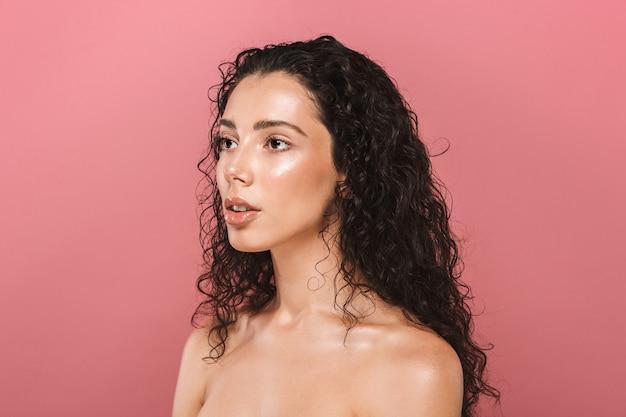 Красивая молодая женщина со здоровой кожей позирует изолированной над розовой стеной, глядя в сторону.