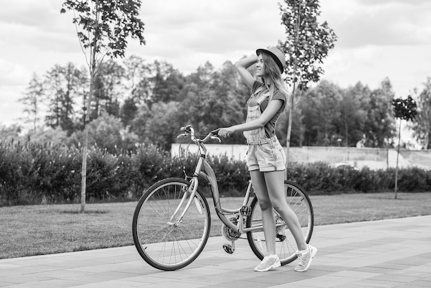Beautiful young woman with her bicycle at the park