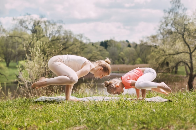 A beautiful young woman with her charming teenage daughter practices yoga outdoors in a park.