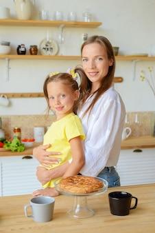 彼女の娘と美しい若い女性は、キッチンの家族のお茶会で朝食を準備します