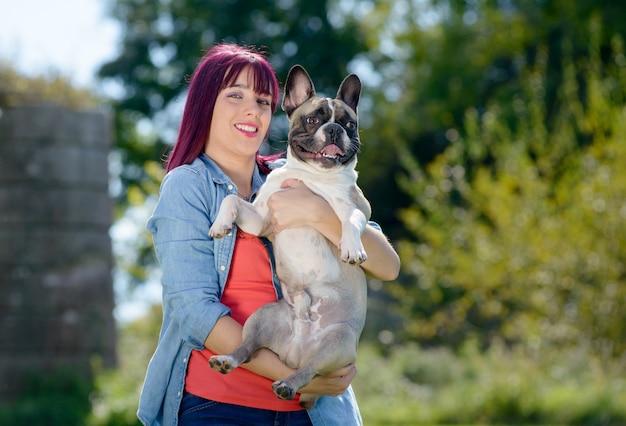 Красивая молодая женщина с ее собакой французский бульдог