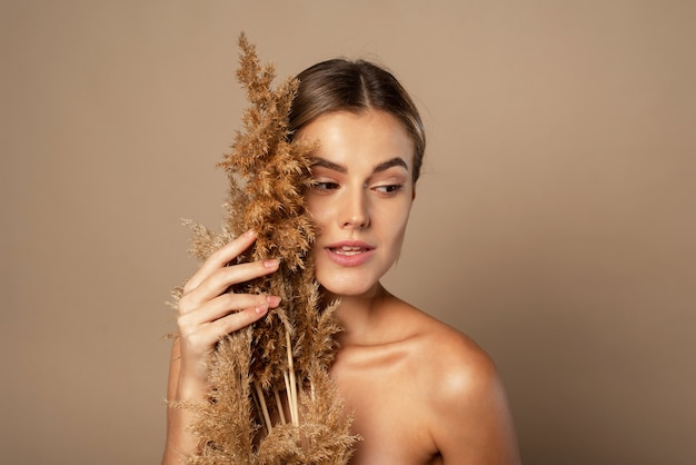 A beautiful young woman with her hair pulled back holds a dry pampas grass in her hands