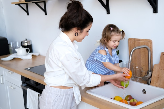 A beautiful young woman with her two year old daughter is washing fruit in the kitchen sink.