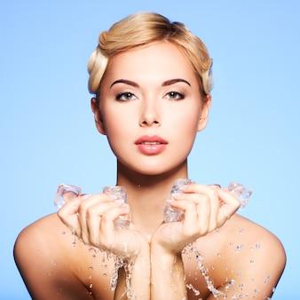 Bella giovane donna con ghiaccio nelle sue mani sul blu.
