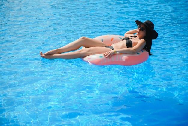 Красивая молодая женщина с надувным пончиком в синем бассейне