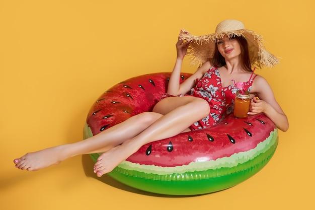 Красивая молодая женщина с надувным кольцом на цветном фоне