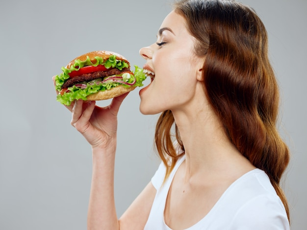 Beautiful young woman with a juicy hamburger in her hands, a woman eating a burger