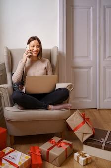 快適な肘掛け椅子に座って携帯電話で話しているラップトップを持つ美しい若い女性