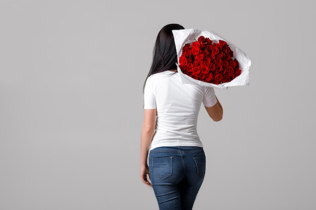 Beautiful young woman with a large bouquet of red roses