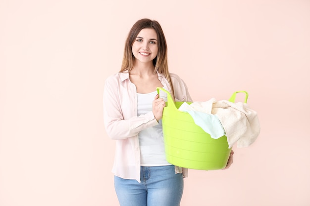 Beautiful young woman with laundry on color