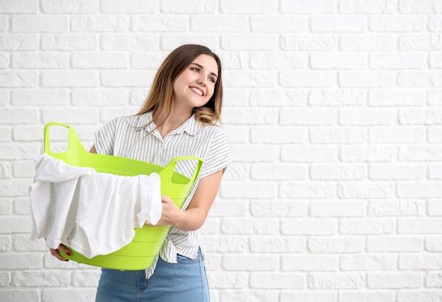 白いレンガの背景に洗濯物と美しい若い女性