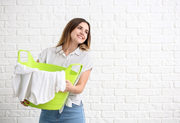 Beautiful young woman with laundry on white brick background