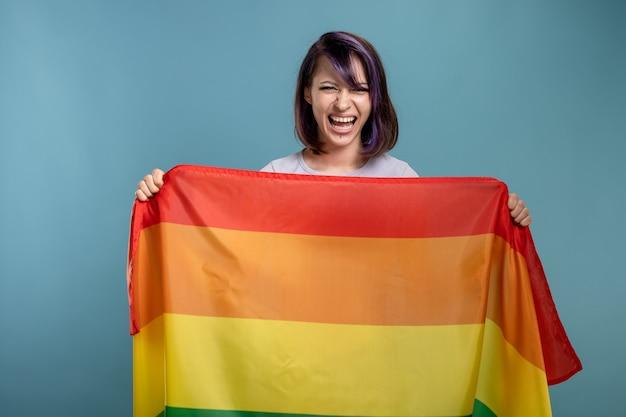 Lgbtの旗を持つ美しい若い女性。染められた紫色の髪とゲイとレズビアンのコミュニティの旗を握っているピアスを持つレズビアン