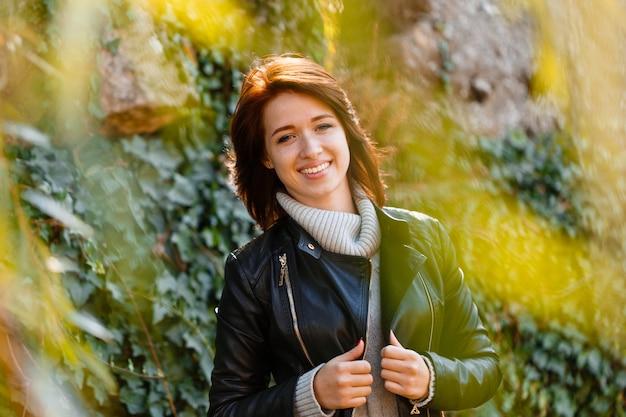 灰色のセーターとbackgrouの黒い革のジャケットの薄茶色の髪を持つ美しい若い女性