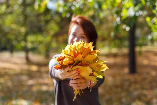 가을 공원 포에서 단풍의 배경에 밝은 갈색 머리 스웨터와 함께 아름 다운 젊은 여자