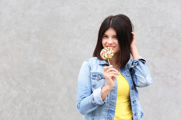 灰色のロリポップを持つ美しい若い女性
