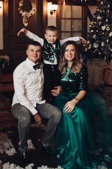 Coctail 드레스에 긴 검은 물결 모양의 머리를 가진 아름 다운 젊은 여자, 흰 셔츠와 청바지에 짧은 검은 머리를 가진 매력적인 강한 남자는 아들과 함께 크리스마스 시간을 보냅니다