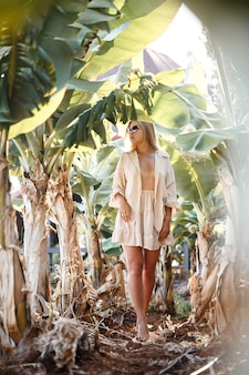 A beautiful young woman with long blond hair of european appearance stands near the banana trees. girl in tropical forest on a sunny summer day