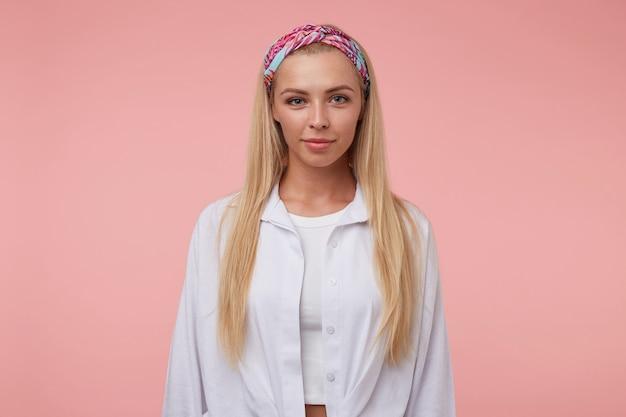 Красивая молодая женщина с длинными светлыми волосами, глядя с мягкой улыбкой, в цветной повязке на голову и белой рубашке, стоя