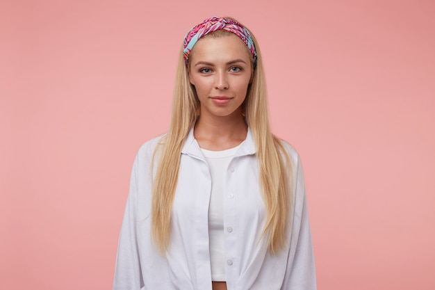 Beautiful young woman with long blond hair looking with soft smile, wearing colored headband and white shirt, standing