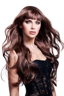 長い茶色の髪の美しい若い女性。スタジオでかわいいモデルのポーズ。