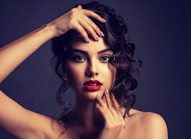 長い巻き毛の茶色の髪とスモーキーなアイメイクの美しい若い女性。スタイリッシュな髪型のセクシーでゴージャスなブルネットの女の子。魅力的な女性の肖像画。ファッションモデル。