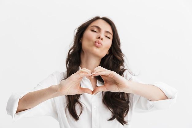 白い壁の上に孤立して立っている白いシャツを着て、愛のジェスチャーを示す長い巻き毛のブルネットの髪を持つ美しい若い女性