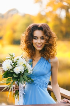 Красивая молодая женщина с длинными вьющимися волосами позирует с букетом