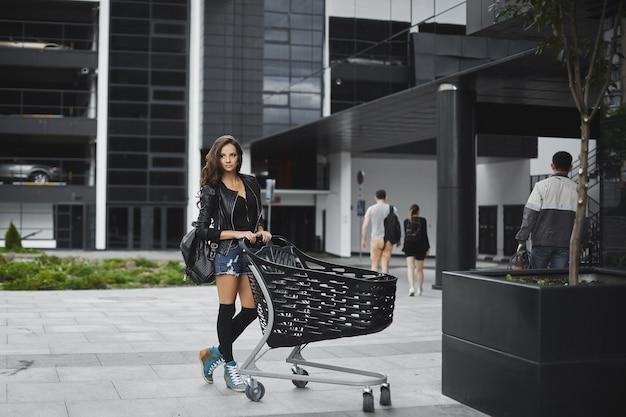 데님 반바지와 가죽 자 켓 야외 상점 근처 쇼핑 카트와 함께 포즈에 긴 검은 머리를 가진 아름 다운 젊은 여자.
