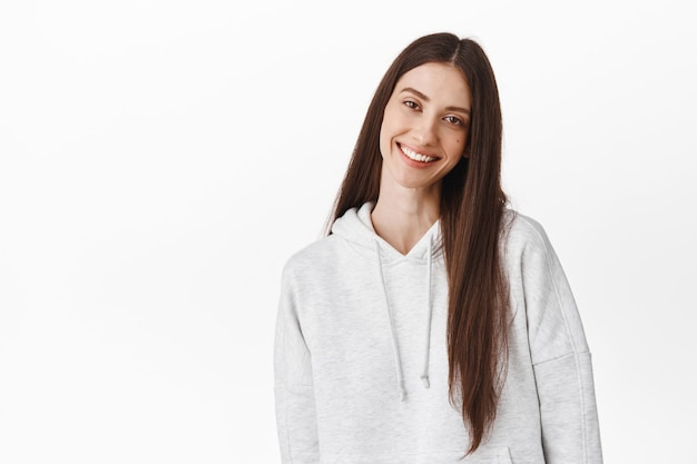 Beautiful young woman with long dark hair, tilt head and smile at front tenderly, standing candid and positive against white wall, wearing hoodie