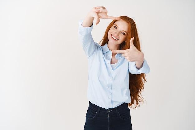 긴 생강 머리와 주근깨가 있는 아름다운 젊은 여성이 손 프레임을 들여다보고 순간을 포착하거나 완벽한 각도를 찾고 흰색 벽 위에 서 있습니다.