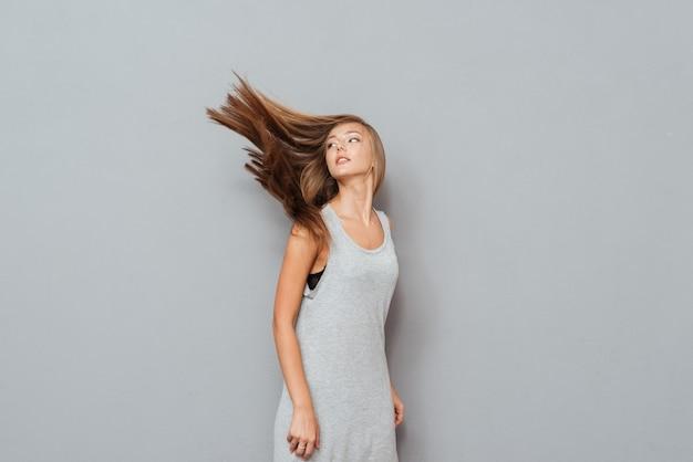 長い髪と目を閉じた美しい若い女性は、灰色の背景で隔離のポーズ