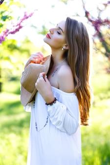 咲く桜の背景に庭で春の晴れた日を楽しんで白いライトドレスで、長い髪の美しい若い女性。スタイリッシュなモデル、リラックス、夢、本当の感情、新鮮な気持ち