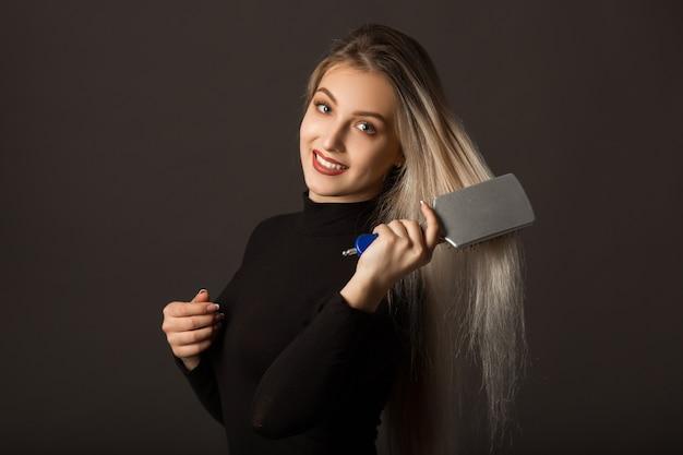 白い背景の上の長い髪の美しい若い女性は彼女の髪をとかす