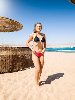 Beautiful young woman with long hair and perfect body standing on the sandy sea beach at looking in camera. girl relaxing and having good time during summer holiday vacation.