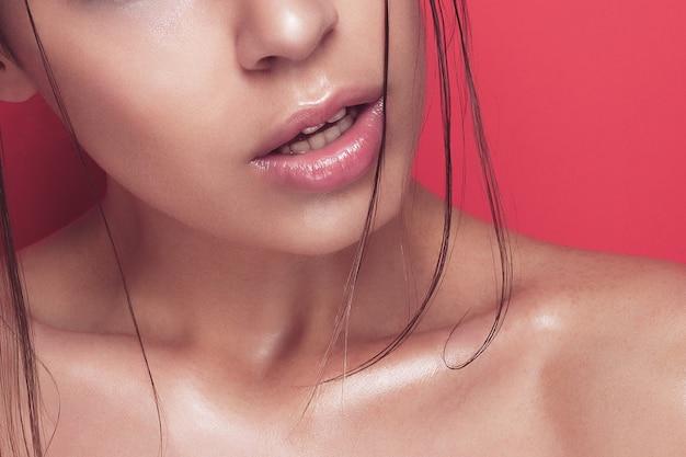 Красивая молодая женщина с длинными волосами позирует на розовом фоне