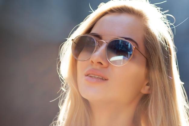 晴れた日に通りでポーズをとって、眼鏡をかけている長い髪の美しい若い女性。テキスト用のスペース