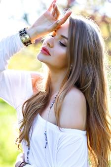 Bella giovane donna con capelli lunghi, in vestito dalla luce bianca che gode della giornata di sole primaverile in giardino su priorità bassa di fioritura di sakura. modello elegante, rilassante, sognante, emozioni vere, sensazioni fresche