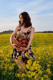 リンゴ、屋外のポートレートが付いているバスケットを保持している黄色の菜の花畑に長い健康的な髪を持つ美しい若い女性。