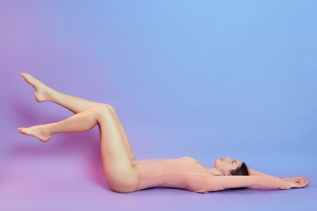 Красивая молодая женщина с длинными ногами в бежевом боди, лежащая на полу и смотрящая вверх, женщина с идеальным телом, поднимающая ноги, позирует изолированной над голубой стеной с розовым неоновым светом.