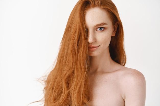 긴 완벽한 빨간 머리와 파란 눈을 가진 아름다운 젊은 여성이 앞을 바라보고 벌거벗은 채 창백한 깨끗한 피부와 자연스러운 이발, 흰 벽을 보여줍니다.