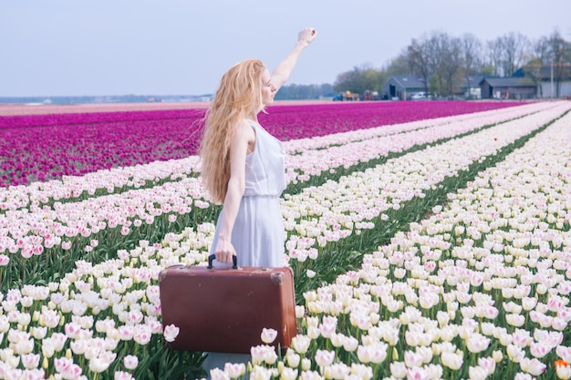 Beautiful young woman with long red hair wearing in white dress standing with luggage on colorful tulip field.