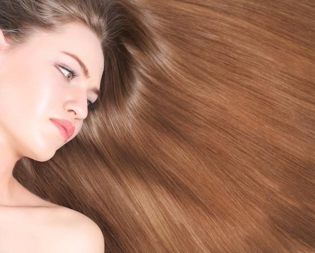 Красивая молодая женщина с длинными прямыми волосами на светлом фоне