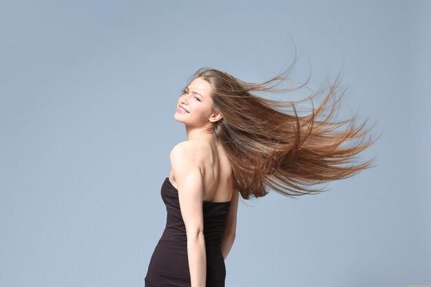 明るい背景に長いストレートの髪を持つ美しい若い女性